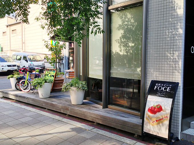 「フォーチェ」のお店の外の風景。お店の入り口横には「北浜スイーツFOCE」と書かれた看板があり、その横から伸びるウッドデッキにはテーブル席がある。