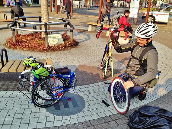 JR守山駅前の広場で、友人がミニベロ「コメットR」を組み立てている様子。その横には折り畳まれた状態の「ニューワールドツーリスト」が置かれている。