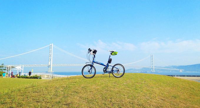 真っ青な空の下に明石海峡大橋が見える、明石・大蔵海岸の風景。緑色の芝生広場の小さな丘の上に、バイクフライデーの青い折り畳み自転車「ニューワールドツーリスト」が停められている写真。