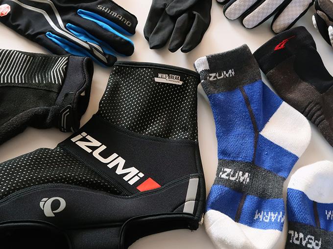 自転車の防寒・寒さ対策のための、冬用グローブやシューズカバーなどウェア小物をいろいろ並べたの写真