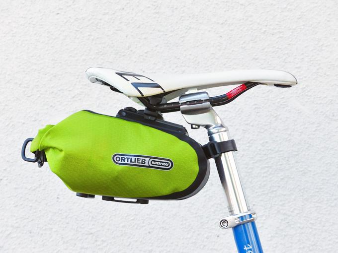 オルトリーブの「サドルバッグM」が、自転車のサドルの下に装着されている様子を横から見た写真。サドルバッグは明るい黄緑色で、「オルトリーブ」のロゴがプリントされている。