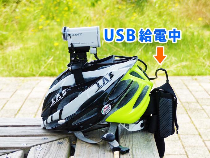 タイトルテキスト「ソニーアクションカムをUSB給電(充電)しながら撮影する方法」と、ヘルメットにマウントされたアクションカムにUSB給電している様子の写真。