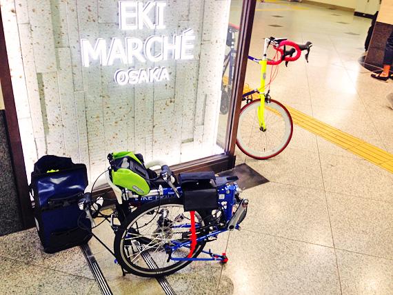 JR大阪駅の構内で、バイクフライデーの折り畳みミニベロ「ニューワールドツーリスト」が小さく折り畳まれている写真。壁には「エキマルシェ」と書かれている。