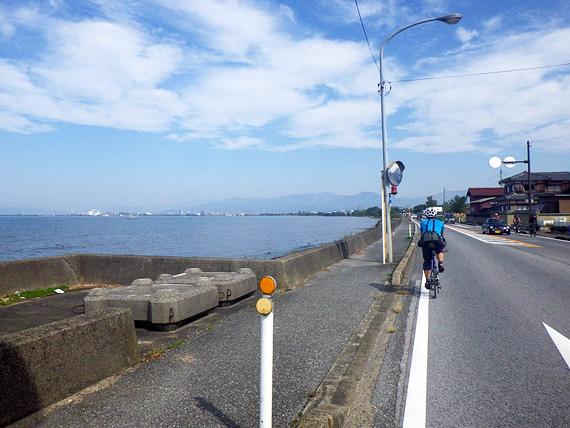 滋賀県米原市の湖岸沿いの道路の写真。左側すぐに琵琶湖の水面が見えている。