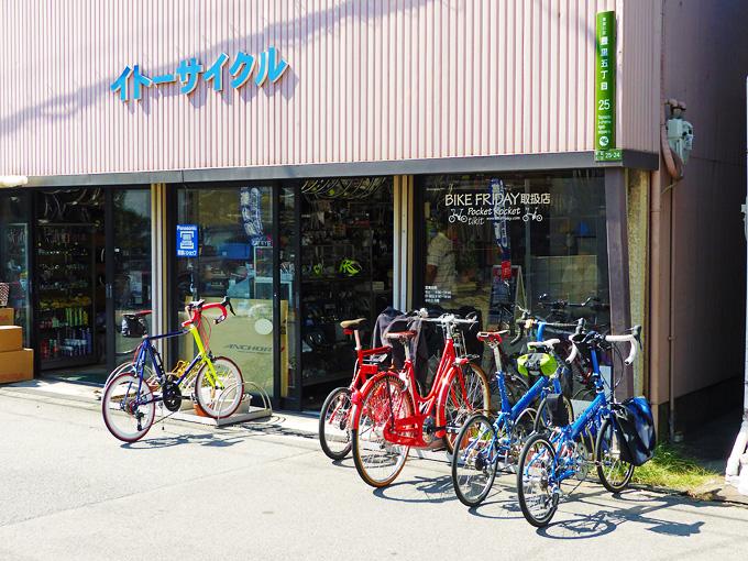 大阪にある自転車屋さん「イトーサイクル」の店舗前の写真。お店の前には筆者の自転車、バイクフライデーの折り畳みミニベロ「ニューワールドツーリスト」と友人の自転車「コメットR」が停められている。お店の窓ガラスには「バイクフライデー取扱店」と書かれている。