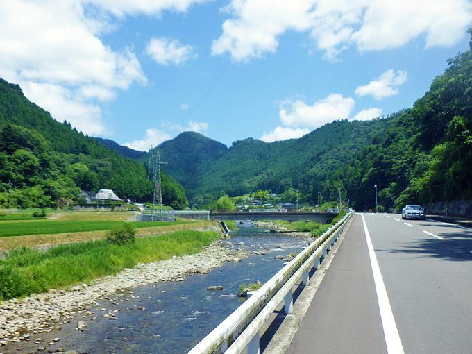 真っ直ぐな道路、ガードレールのすぐ横には川が流れていて、景色のむこうには濃い緑色の山が見える。その上には青空が広がっている。