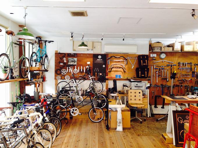 大阪の南堀江にある自転車屋さん「ヴェロライフ・アンプ」の店内の写真。白い壁に木製のパネルや装飾がされていて、窓辺には商品の自転車がたくさん飾られ、壁には自転車の部品やアクセサリーなどがたくさん吊り下げられている。