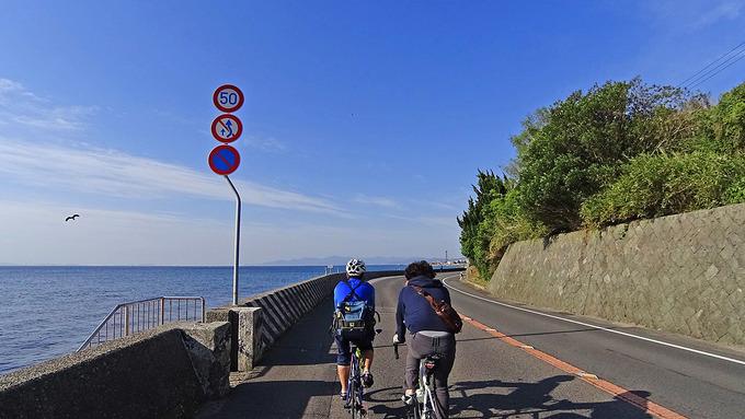 淡路島・釜口付近の道路から見た風景の写真。ゆるやかにカーブした道路のすぐ外側には青い海が広がっている。