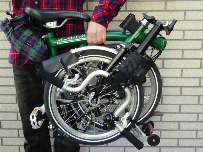 折りたたみ状態の折りたたみ自転車「ブロンプトン」を片手で持ち上げている様子