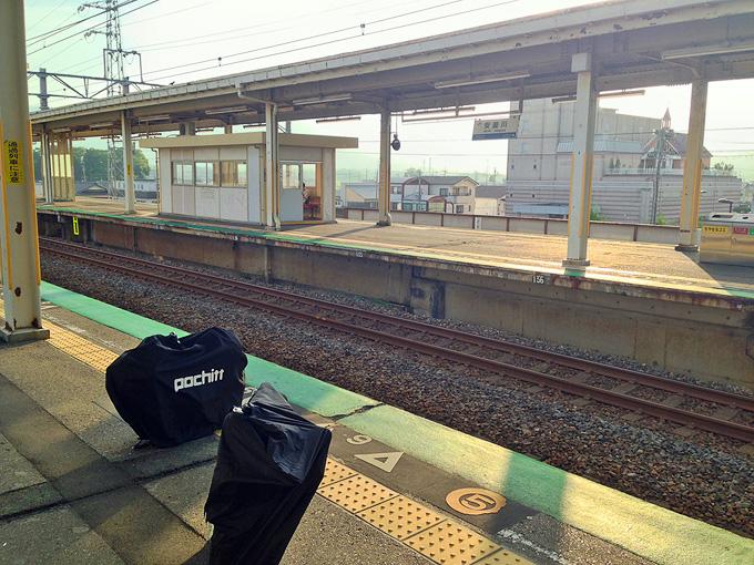 駅のホームに、自転車が入った輪行袋が2つ置かれている写真。