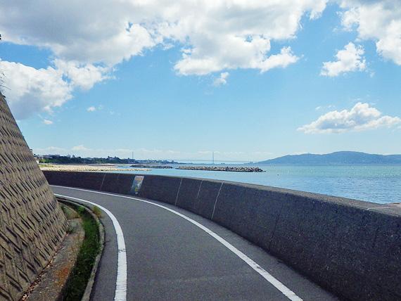播磨サイクリングロードの道路の写真。左にカーブしていてその先は見えない。右側は青い海が広がっている。遠くに明石海峡大橋が見える。