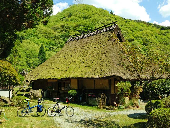 三田にある軽食処「峠の茶屋・一軒家」の店舗外観の写真。昔ながらの茅葺の建物で、あちこち緑色に苔がついている。手前には2台の自転車、ニューワールドツーリストとコメットRが停められている。
