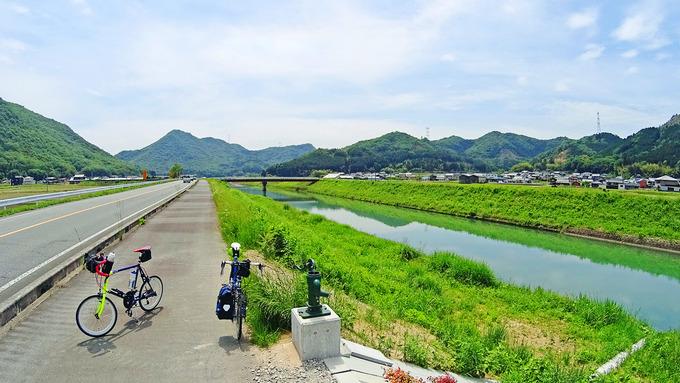 田舎道を流れる川辺に2台の自転車、「ニューワールドツーリスト」と「コメットR」が停められている。
