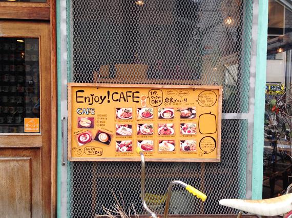 大阪の南堀江にある飲食店「エンジョイ・カフェ」の入り口の写真。掲示板のようなものに、お料理の写真や説明が書かれている。上には大きく「エンジョイ・カフェ」と書かれている。