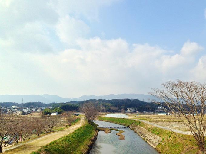 滋賀県大津市を流れる「真野川」に架かる橋の上から見た風景の写真。綺麗な川と広大な農地が見える。
