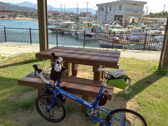 淡路島の「炬口漁港」付近の公園の風景。緑色の芝生広場で、茶色のベンチがある。景色の向こうにはたくさんの漁船が停泊しているのが見える。
