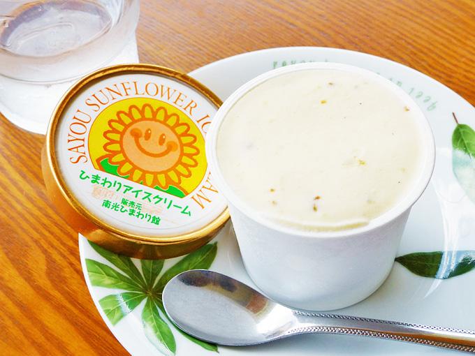 蓋が開けられたカップアイスクリームの写真。蓋には「ひまわりアイスクリーム」と書かれている。アイスクリームは、白いバニラアイスの中に、ひまわりの種が入っているのがところどころ見えている。