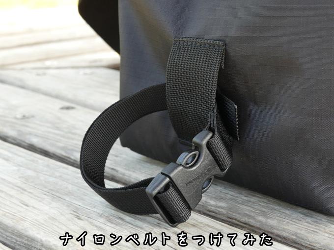 バッグ背面のベルトループに「クイックリリース付きのナイロンベルト」が装着されている写真。