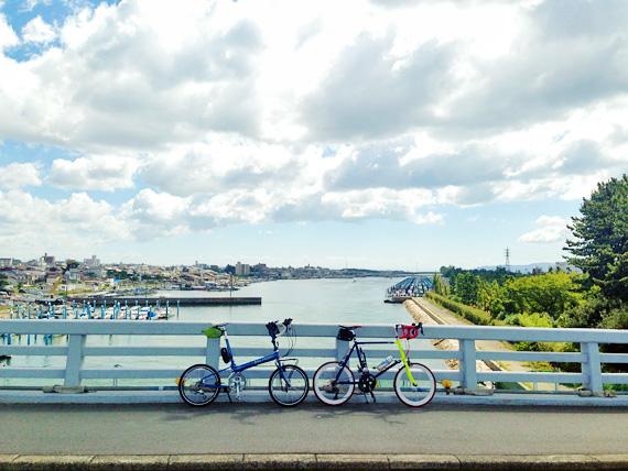 兵庫県明石市二見町の東二見人工島へと続く橋の上から見る風景の写真。橋の上には2台の自転車、バイクフライデーの折り畳みミニベロ「ニューワールドツーリスト」とフジのミニベロロード「コメットR」が停められていて、むこうには海が見え、たくさんの小型船が停泊しているのが見える。