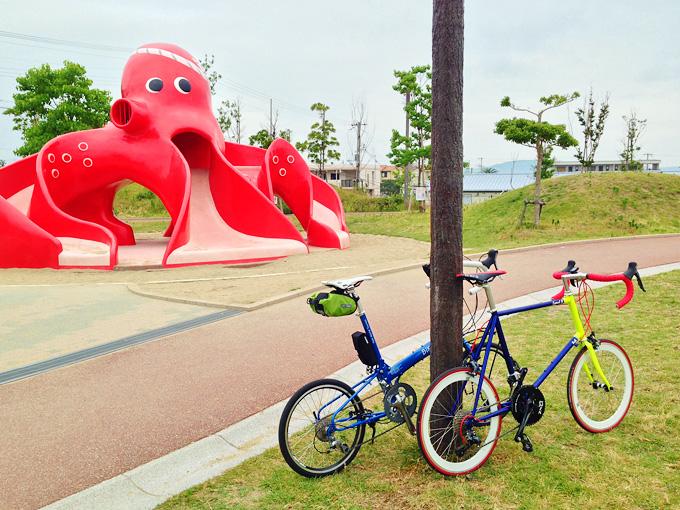兵庫県明石市の海辺にある松江公園の写真。芝生の広場に2台の自転車が停められている。むこうには巨大な赤いタコの形をした遊具が見える。