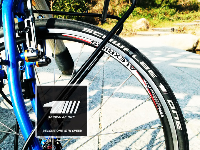 シュワルベ製の高性能タイヤ「シュワルベワン」の451サイズが装着されたミニベロのフロントタイヤ付近を写した写真。タイヤにはシュワルベワンという文字がプリントされている。