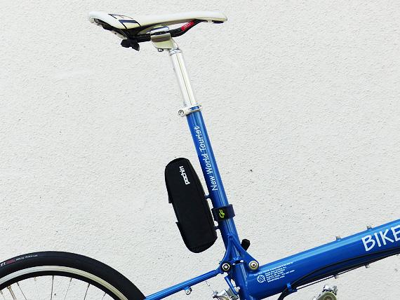 バイクフライデーの折り畳みミニベロ「ニューワールドツーリスト」のシートマスト周辺を真横から見た写真。上下に長い青いパイプで、パイプの上には銀色のシートポストと白いサドルが装着されている。青いパイプの下部は、折り畳み機構のヒンジやクイックレバーが見える。