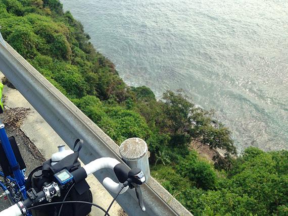 ガードレールの外側を見下ろした写真。断崖絶壁で、はるか下のほうに海が見える。