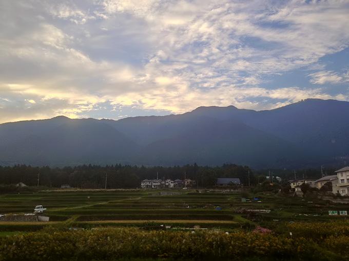 JR湖西線の車窓から見た夕方の田舎の風景。すっかり陽が落ちて、薄暗い景色の中に棚田が見える。むこうには山の稜線と、そのむこうに夕焼け色の雲が見える。