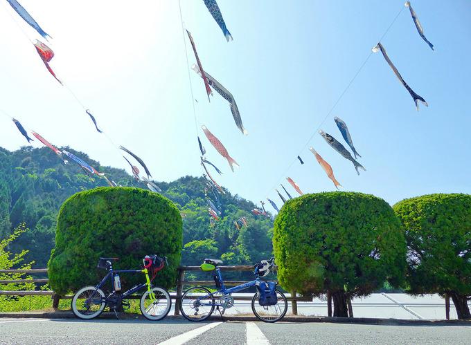 神河町「グリーンエコー笠形」の鯉のぼりがある風景。手前には2台の自転車、「ニューワールドツーリスト」と「コメットR」が停められている。