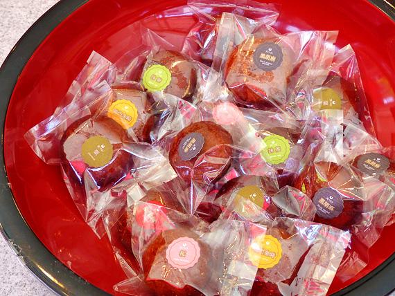個包装された揚げ饅頭がたくさん。中の餡の種類を示す色とりどりのシールが、それぞれの包装に貼られている。