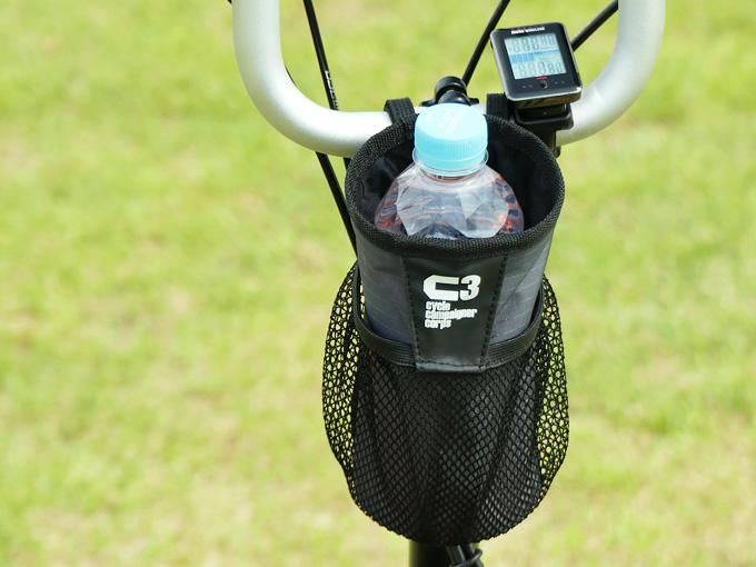 BROMPTON(ブロンプトン)にボトルケージとして使えるアイテム「ハンドルセンターポーチ」が装着されている写真。例としてペットボトルを収納してボトルケージとして使用している様子。
