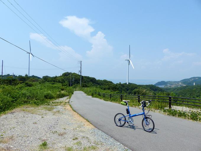 山の稜線に建てられた風力発電用の巨大な白い風車。風車が並ぶ風景をバックに、青い自転車「ニューワールドツーリスト」が停められている。稜線の合間に見える景色のはるかむこうには、青い海の水平線が少しだけ見える。