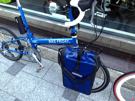 バイクフライデーの折り畳みミニベロ「ニューワールドツーリスト」のフロントホイール右側にオルトリーブのパニアバッグ「フロントローラークラシック」が装着されている写真。