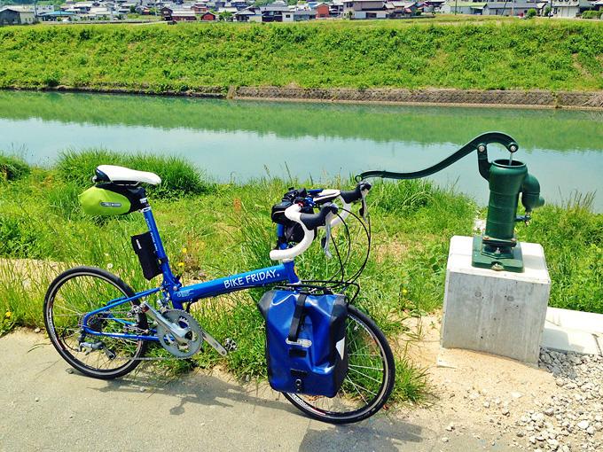 川の横の歩道脇に、手動式の井戸水ポンプがある写真。