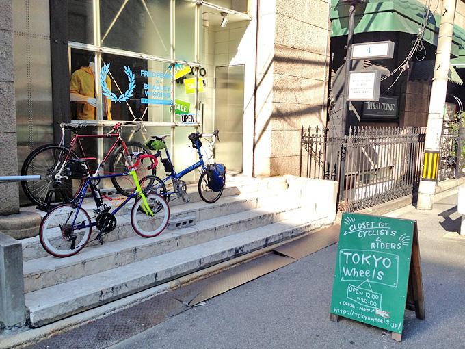 大阪にある自転車アイテムショップ「トーキョーウィールズ大阪店」の店舗前の写真。入り口の雛壇状の階段にバイクフライデーの折り畳みミニベロ「ニューワールドツーリスト」と友人の自転車「コメットR」が停められている。