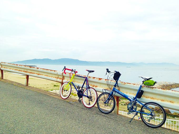 砂浜と海を眼下に見下ろせる海辺の高台で、ガードレールに立てかけて停められた2台の自転車の写真。むこうには淡路島が青白く霞んで見える。