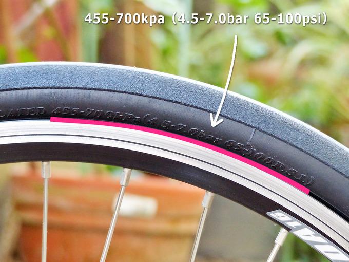 自転車のタイヤの側面に適正空気圧(指定空気圧)の表示があることを示した写真。