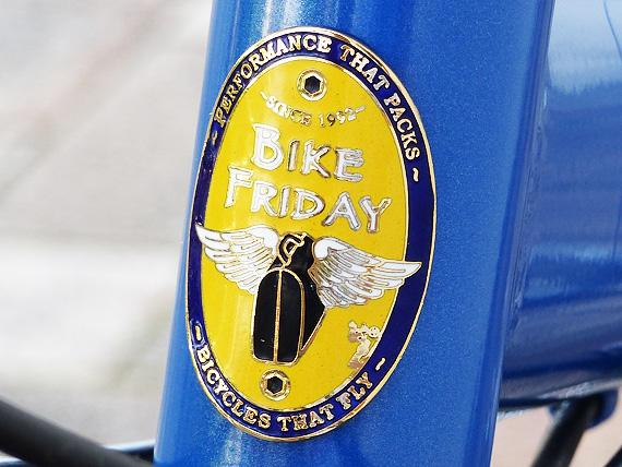 バイクフライデーの折り畳みミニベロ「ニューワールドツーリスト」のフレームの最前部であるヘッドチューブに貼り付けられたバイクフライデーのエンブレムの写真。エンブレムは七宝焼きで、黄色や青、白、金色などで細かく文字や絵が描かれている。