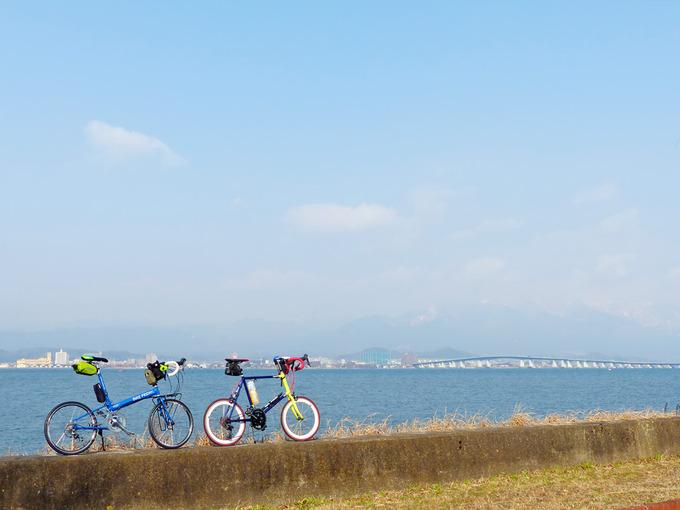 青い琵琶湖の水が広がる風景のむこうに、琵琶湖大橋が見える。手前には2台の自転車、「ニューワールドツーリスト」と「コメットR」が停められている。