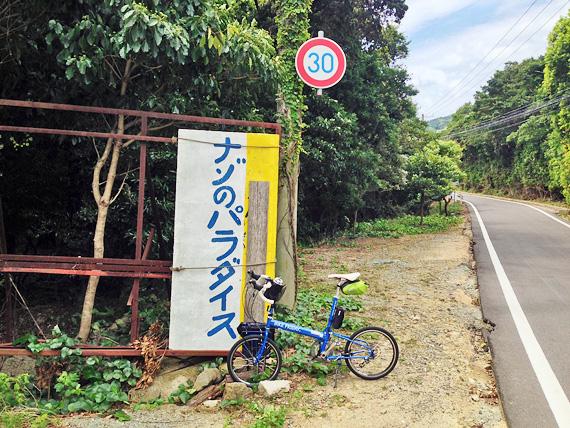 淡路島・洲本市南部の道路脇の風景。木の下に大きな看板があり、「ナゾのパラダイス」と書かれている。