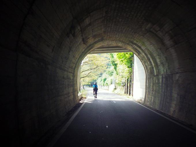 「海津大崎」を走る道のトンネル内の写真。すぐ先はトンネルの出口で明るい風景が見えている。