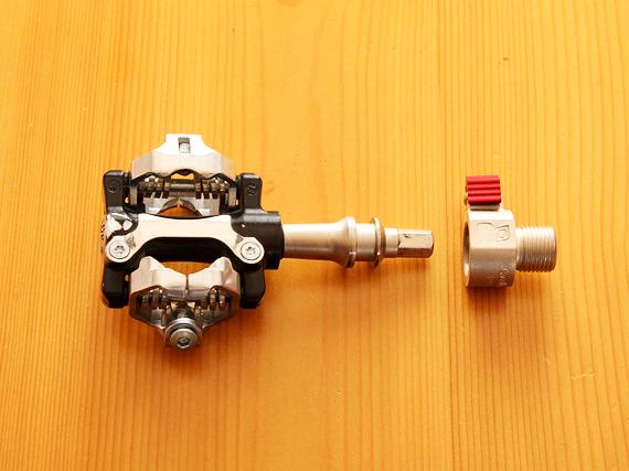 「Wellgo(ウェルゴ)」の着脱式ペダル「QRD」のペダルの、SPDビンディングペダルタイプとアダプターが1つずつ置かれた写真。