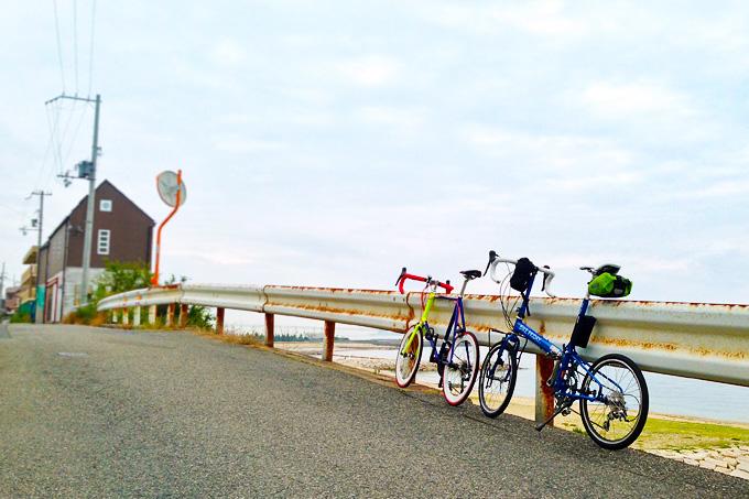 砂浜と海を眼下に見下ろせる海辺の高台で、ガードレールに立てかけて停められた2台の自転車の写真。