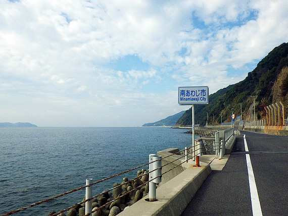 淡路島の南部「南淡路水仙ライン」の道路の写真。「南あわじ市」と書かれた道路標識が立っている。