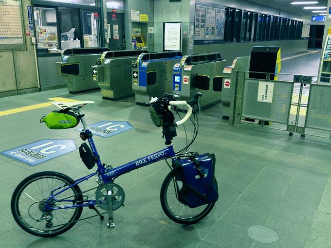早朝のJR「朝霧駅」の様子。誰も居ない薄暗い改札口の前にバイクフライデーの折り畳みミニベロ「ニューワールドツーリスト」が停められている。