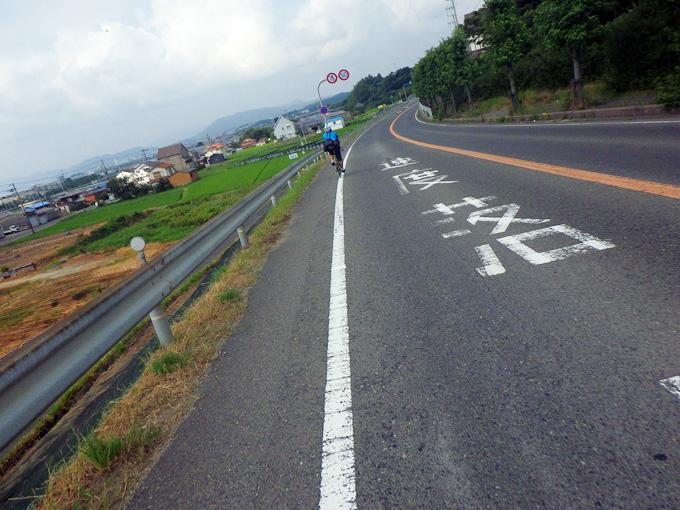 黒いアスファルトの道を、友人が乗った自転車が走ってゆく。道路の左側には田畑が見える。