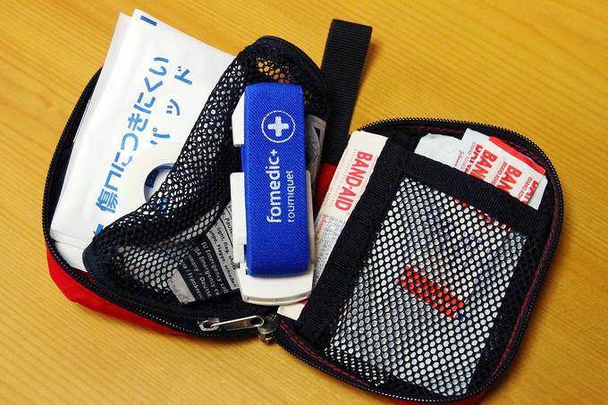 赤色の小さなポーチ「ドイター・ファーストエイドキットバッグS」に、色々なファーストエイド用品が収納されている写真。
