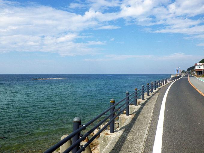 淡路島の西側の道路の風景。道路の左側に青い海が広がっている。