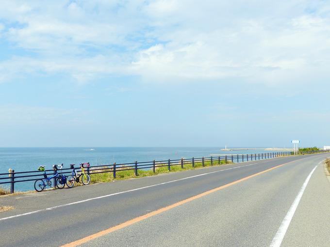 淡路島の西側の海岸線の風景。まっすぐな道路の左側には青い海が広がっている。