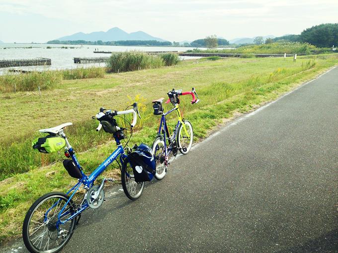 滋賀県近江八幡市内の湖岸道路から見た風景。左には草むらと琵琶湖が見える。手前にはバイクフライデーの折り畳みミニベロ「ニューワールドツーリスト」と、ミニベロロード「コメットR」が停められている。